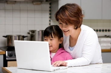 Child and adult looking at a computer